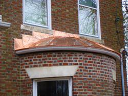 Round standing seam roof section in copper