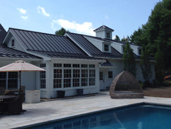 Standing seam matte black aluminum roofing with colorgard snow retention system and single bead gutter