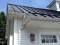 Standing seam matte black aluminum roofing with colorgard snow retention system and single bead gutter - view 6